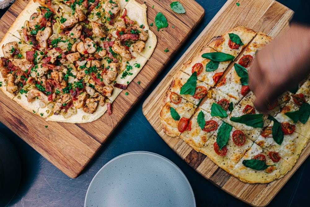 two leafy vegetable pizzas